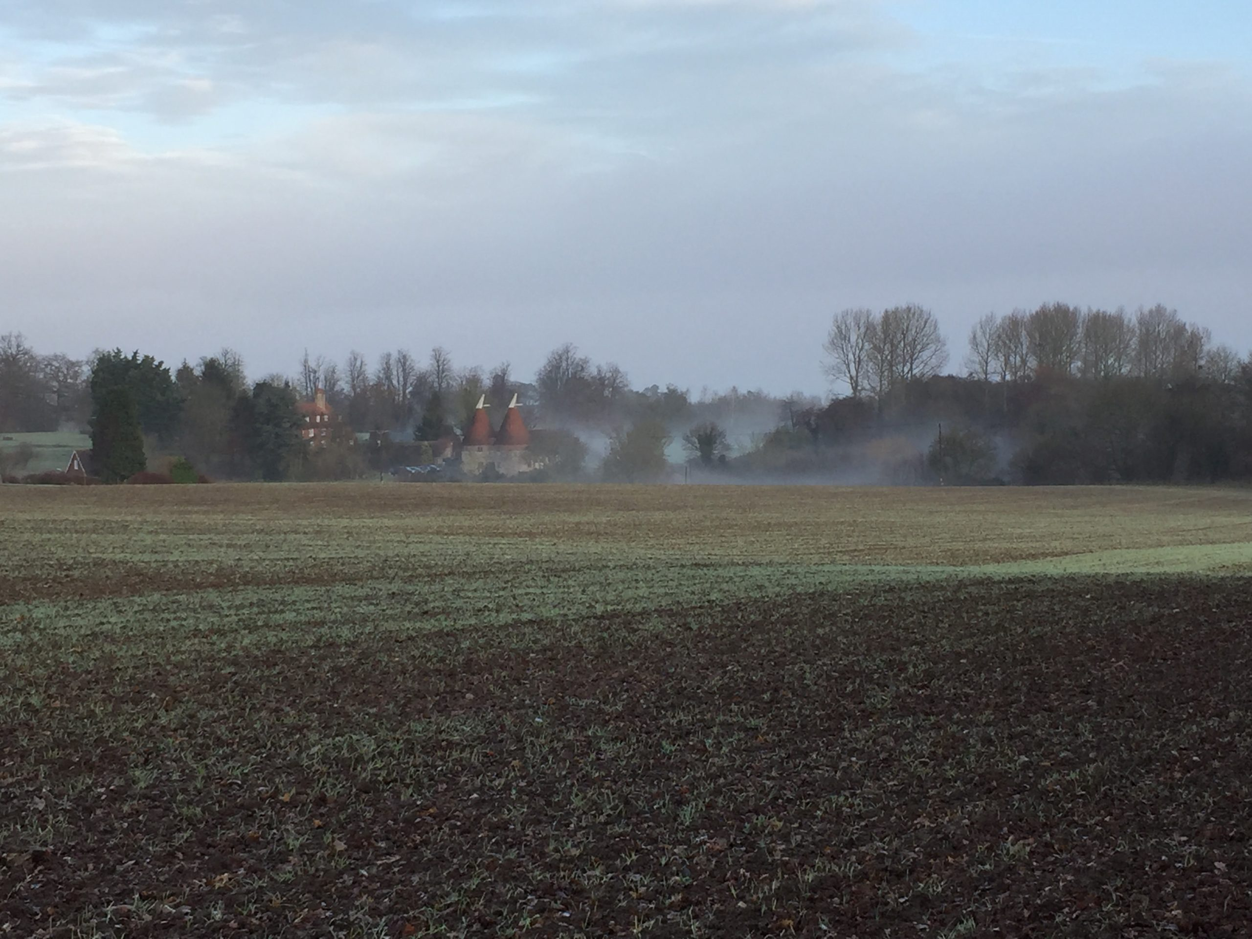 Bowley Oast with Bowley Farmhouse behind on a mist morning